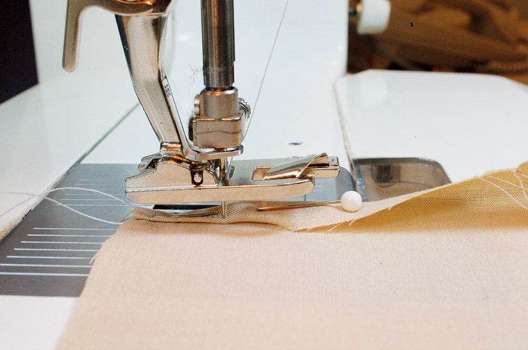 4. Take two to three stitches, turning the flywheel toward you by hand, near the inside folded hem edge and just left of the pin. Stop with the needle down, lift the presser foot, and remove the pin.