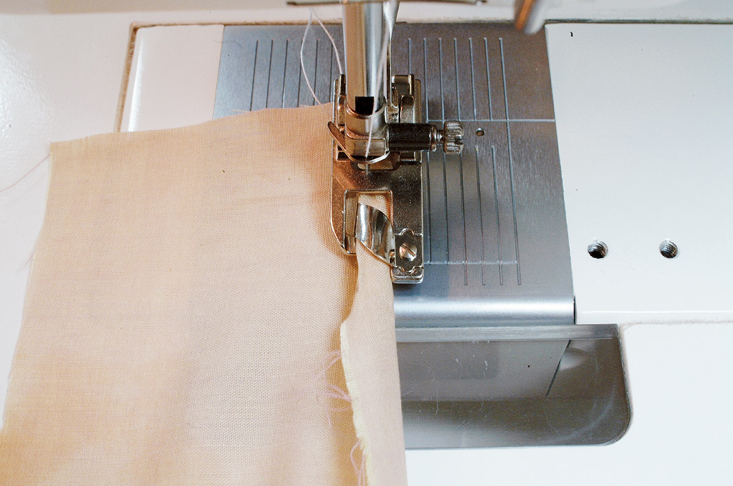 5. Feed the fabric edge into the curl of the hemmer, pulling gently on the fabric in front of the foot.