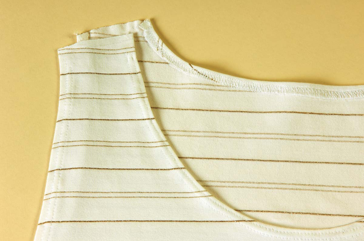 Use a double needle to finish the armholes, neckline, and hem