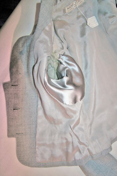 Inside the jacket, a satin facing at the back neck ensures comfort and underarm shields protect the lining.