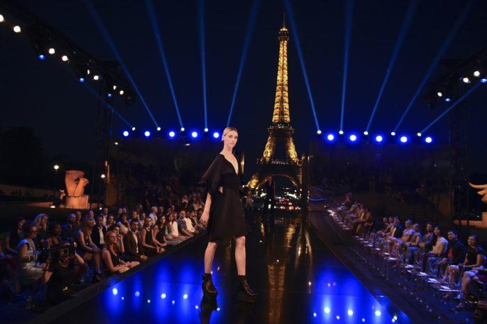 Model in black dress on runway with lit-up Eiffel Tower in background