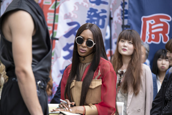 Making the Cut Judge Naomi Campbell looking at model in black streetwear outfit with Tokyo street signs as a backdrop