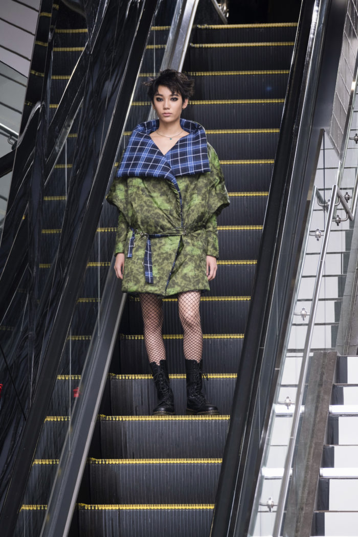 Model on an escalator wearing a green print puffer jacket with contrasting blue-and-black plaid neckline and collar facing