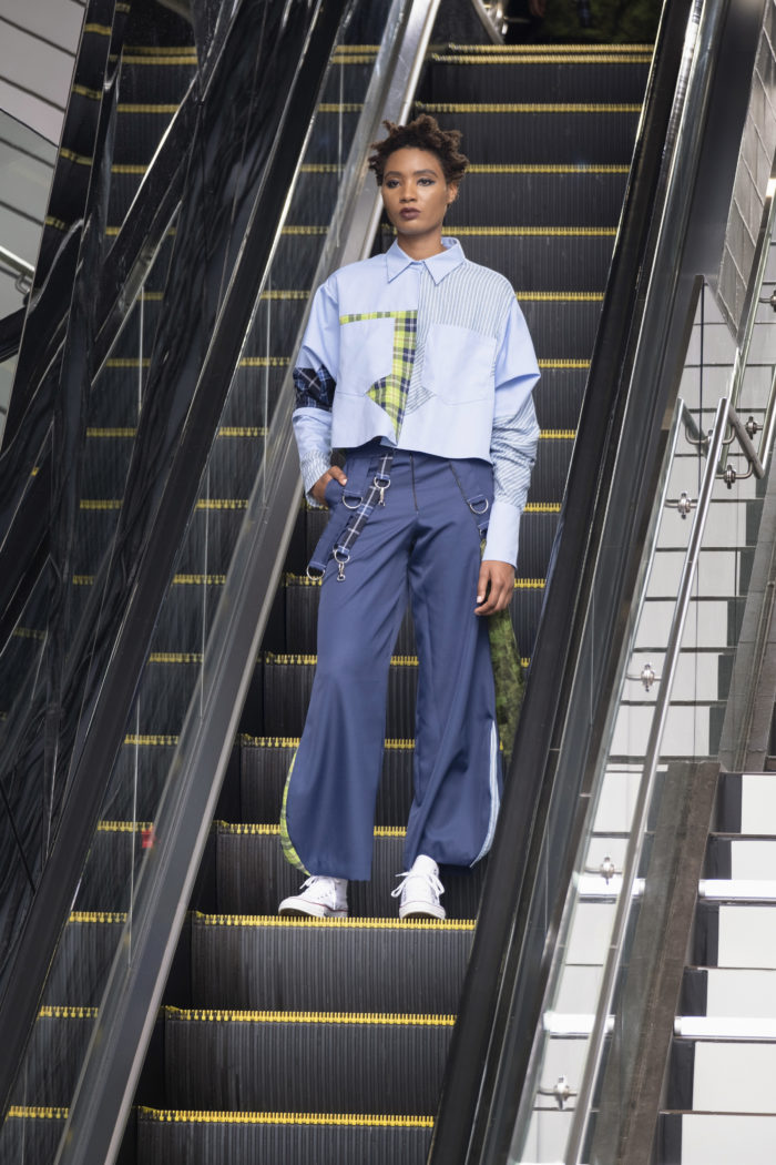 Model on escalator in streetwear, a loose-fitting button-front top and gray pants, and white sneakers