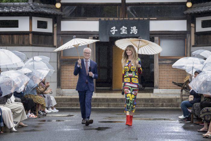 "Tim Gunn and Heidi Klum walking toward camera in the rain, each holding a wagasa, or Japanese umbrella, aloft in ""Digital Marketing Campaign"" episode"