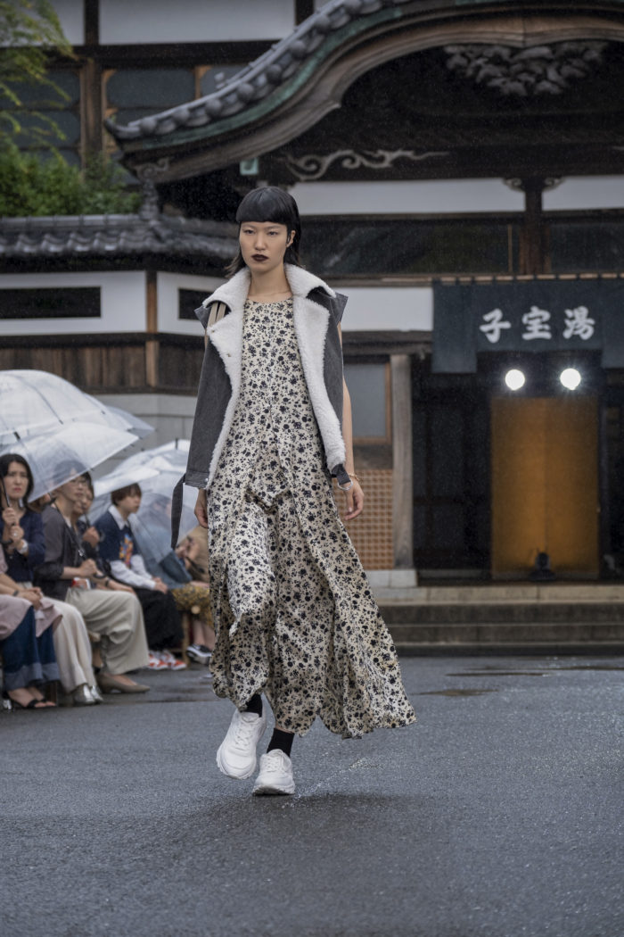 Female model wearing long floral dress with open vest over it