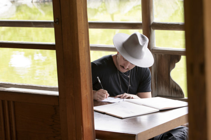 Jonny Cota sitting near a window sketching on paper in Making the Cut Brand Evolution episode