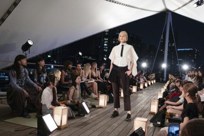 Model on the runway wearing white short-sleeve shirt, black tie, black cropped pants