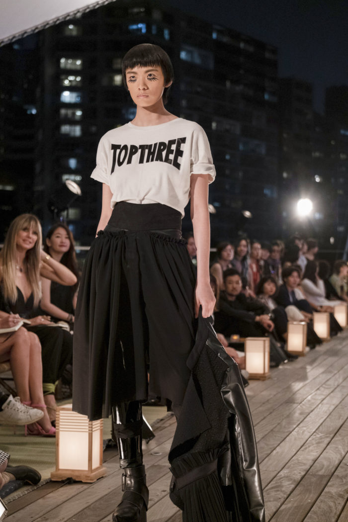 """Female model wearing white T-shirt with the words """"Top Three"""" in Making the Cut """"Brand Evolution"""" episode"""