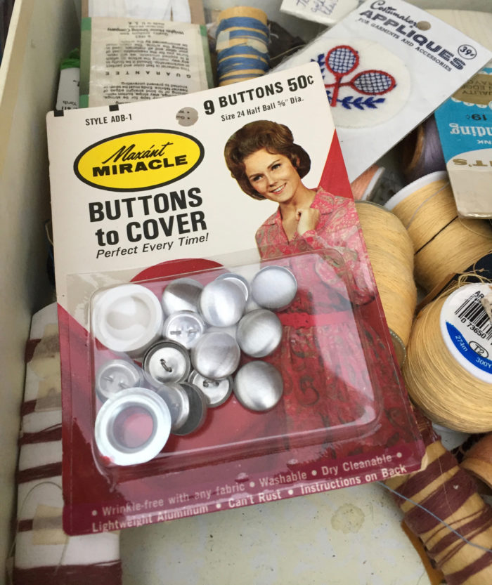 Button covers in original packaging picturing a woman home sewer