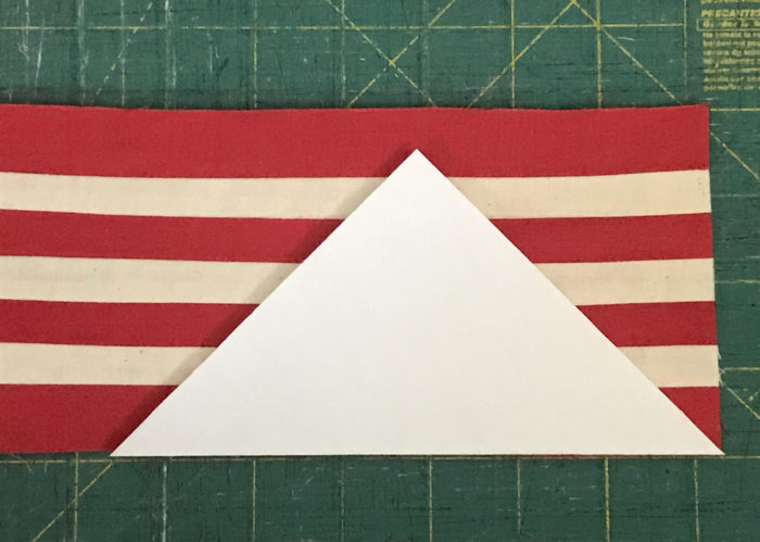 Paper triangle pattern lying on top of red-and-white-striped fabric