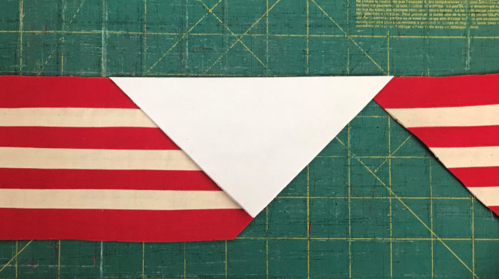 Triangles being cut from red-and-white striped fabric
