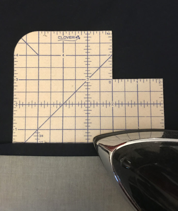 Place mat backing edges being pressed in 1/2 inch
