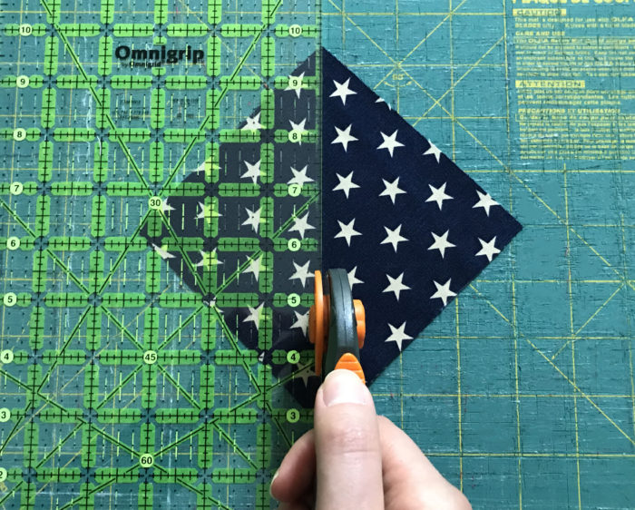 Rotary cutter cutting square of blue and white star fabric on a cutting mat