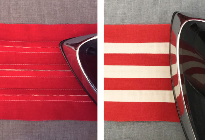Wrong side and right side of sewn together red and white fabric strips being pressed by iron