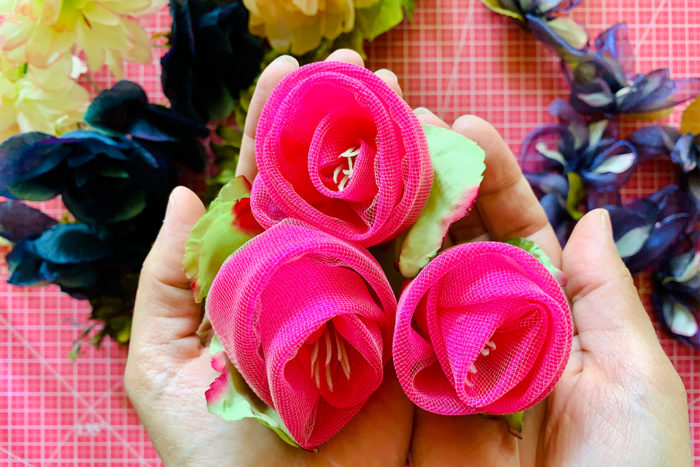 Three hot pink fabric roses held in cupped hands