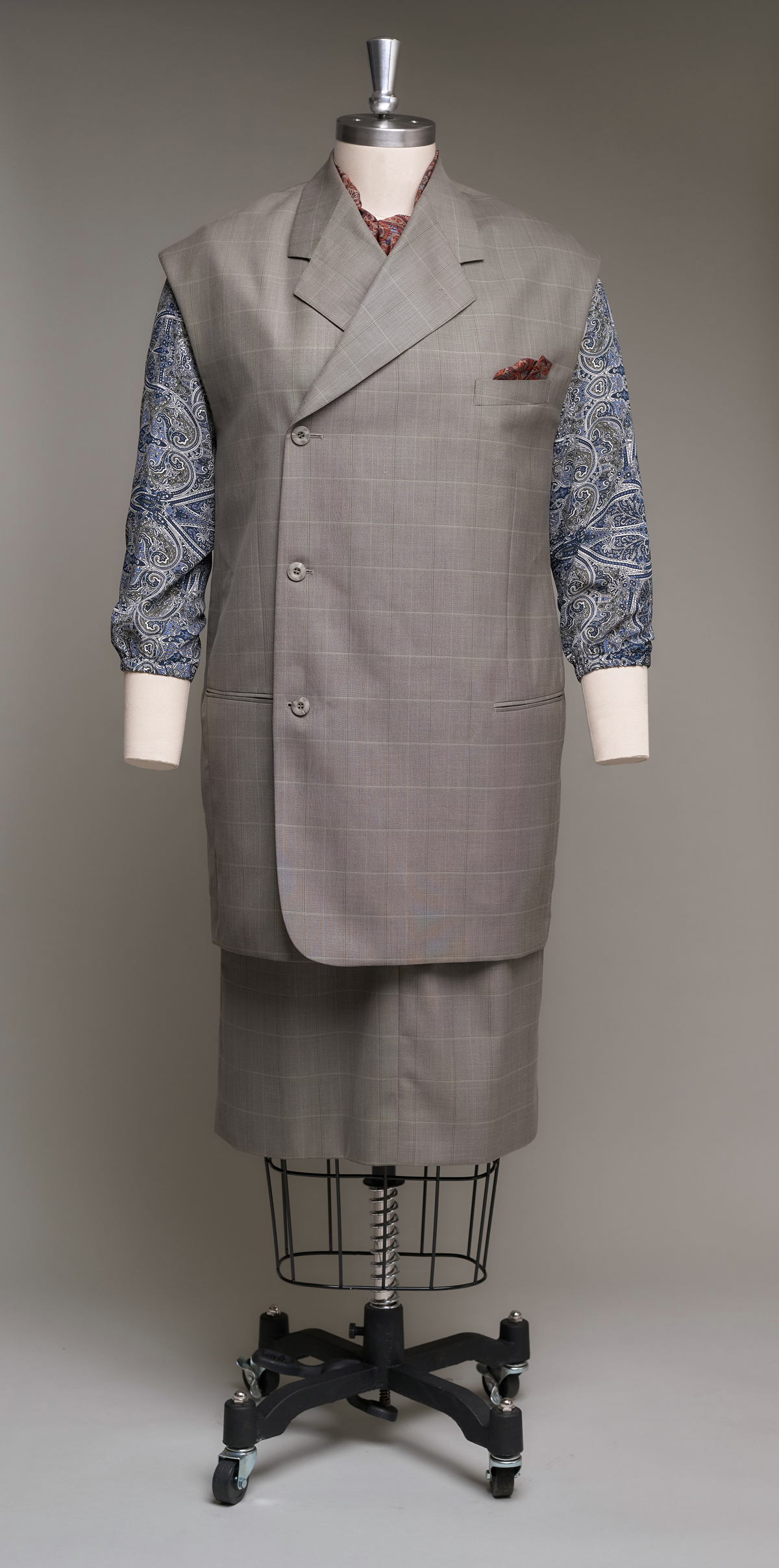 Sleeveless women's suit with paisley blouse on dress form