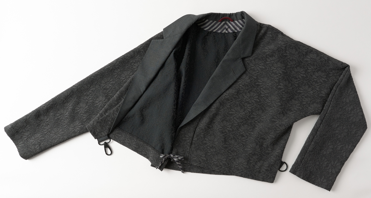 Jacket lying on table with one side open to reveal tie closure