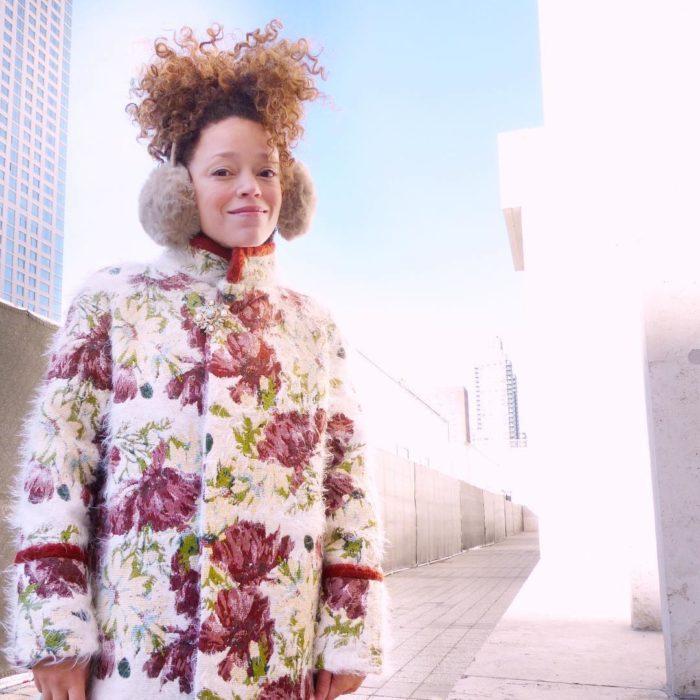 Woman in ear muffs wearing large-scale print winter coat