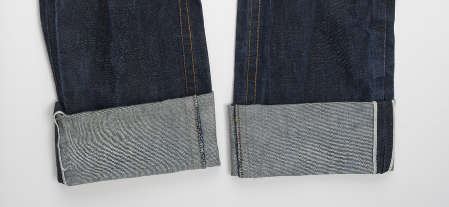 Close-up of cuffed denim jeans, revealing the selvage along the outside seams