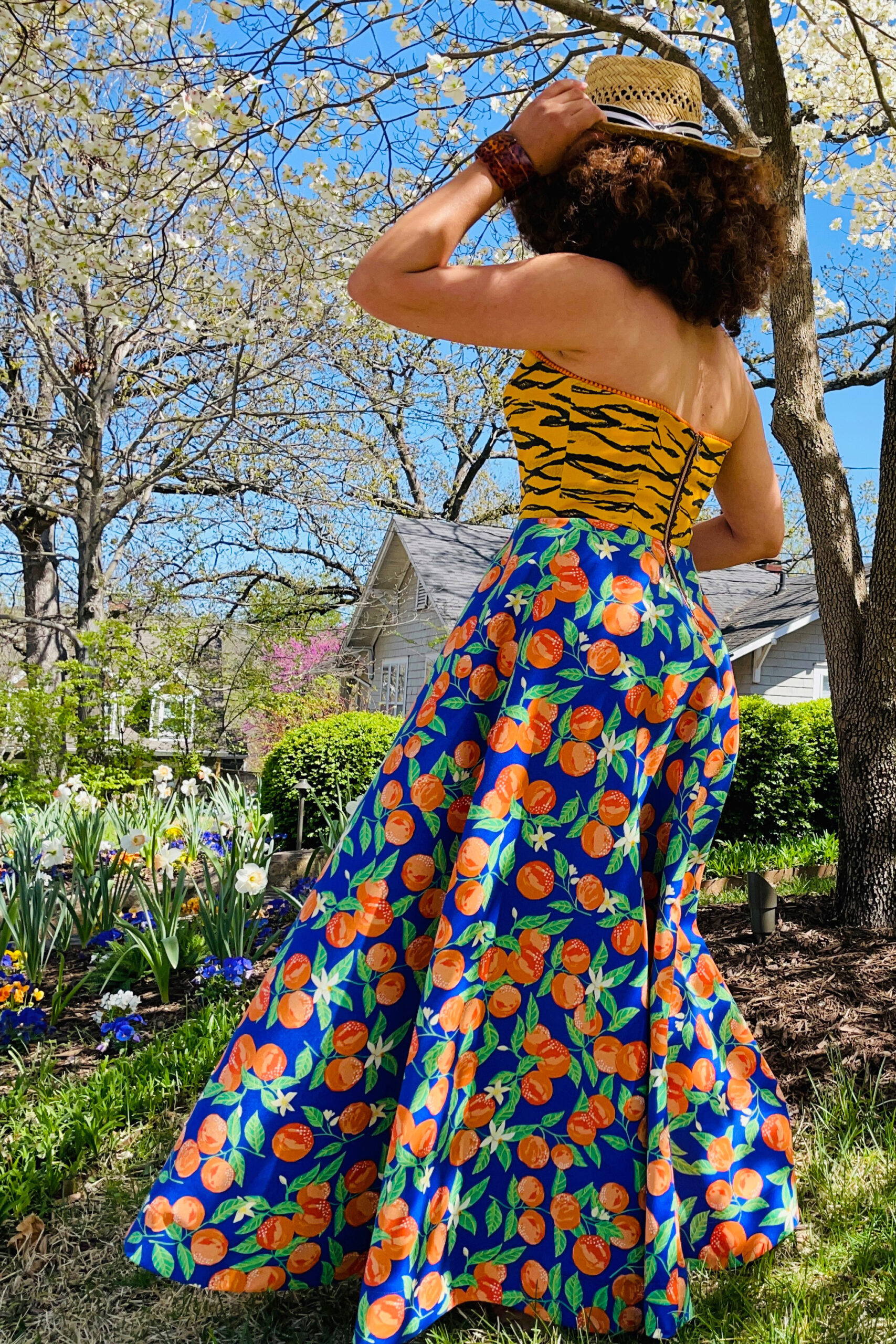 Back view of Marcy Harriell wearing colorful strapless dress and a straw hat