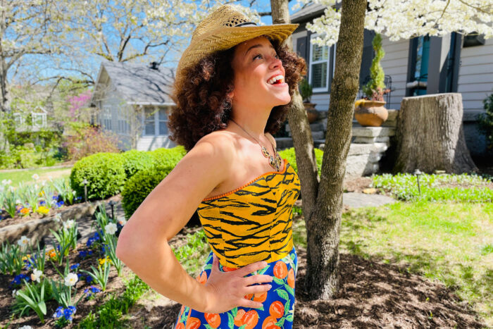Brilliant decorating: Marcy Harriell looking skyward as she stands in front of a bloom dogwood wearing a colorful dress of her design.