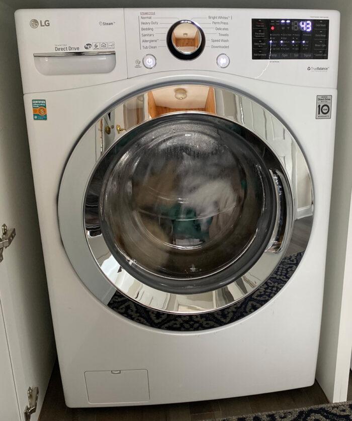 Washing fabrics: front of washing machine as it washes clothing