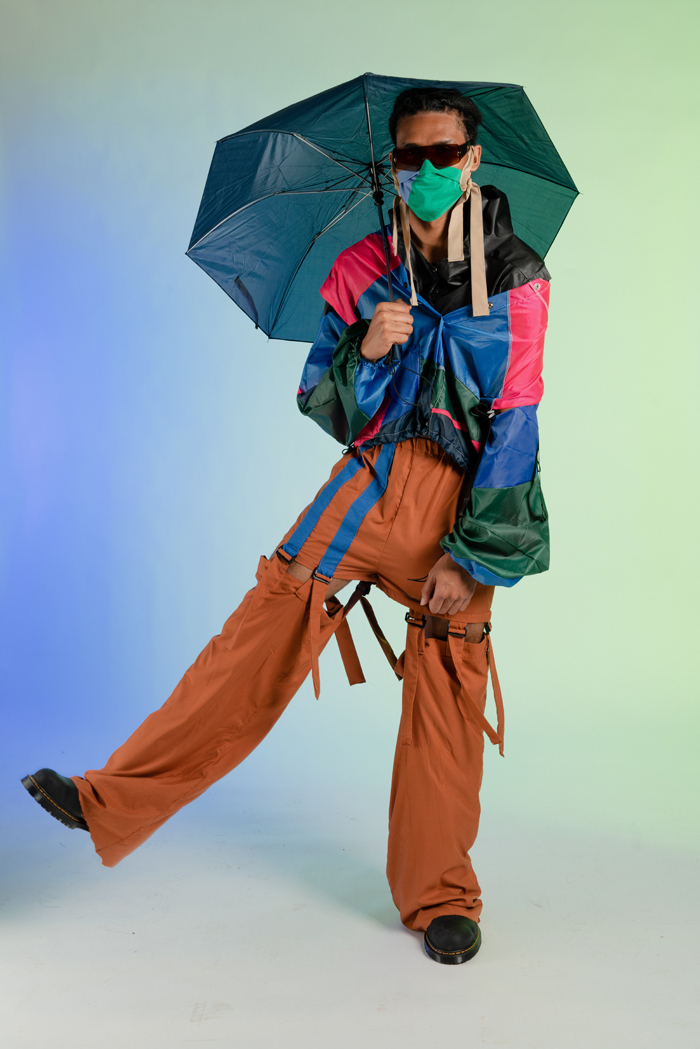 Model holds an open umbrella and wears garments made from patterns in the Open Source Fashion Cookbook
