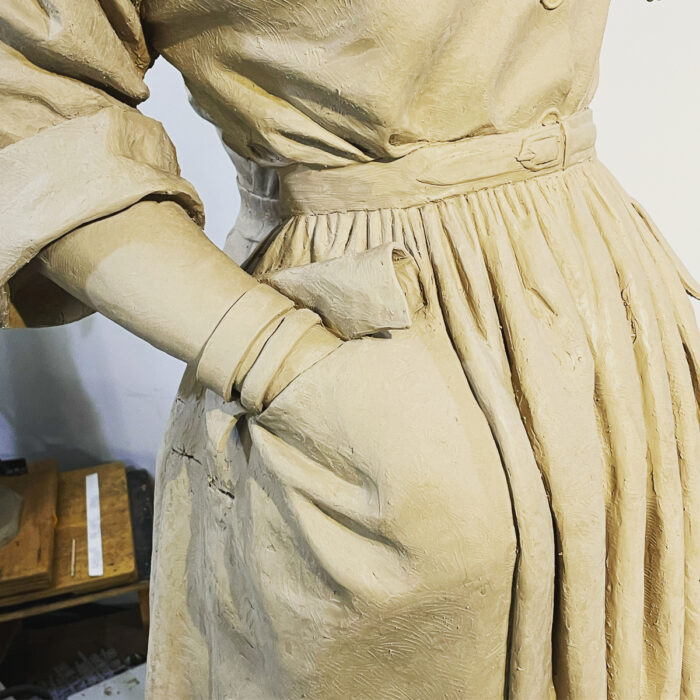 Close-up of Claire McCardell sculpture shows the figure's right hand in the dress's pocket