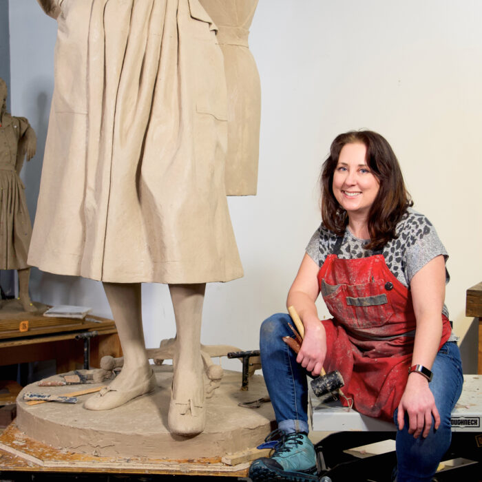 Sculptor Sarah Hempel Irani sits at the base of her Claire McCardell depiction which will be cast in bronze