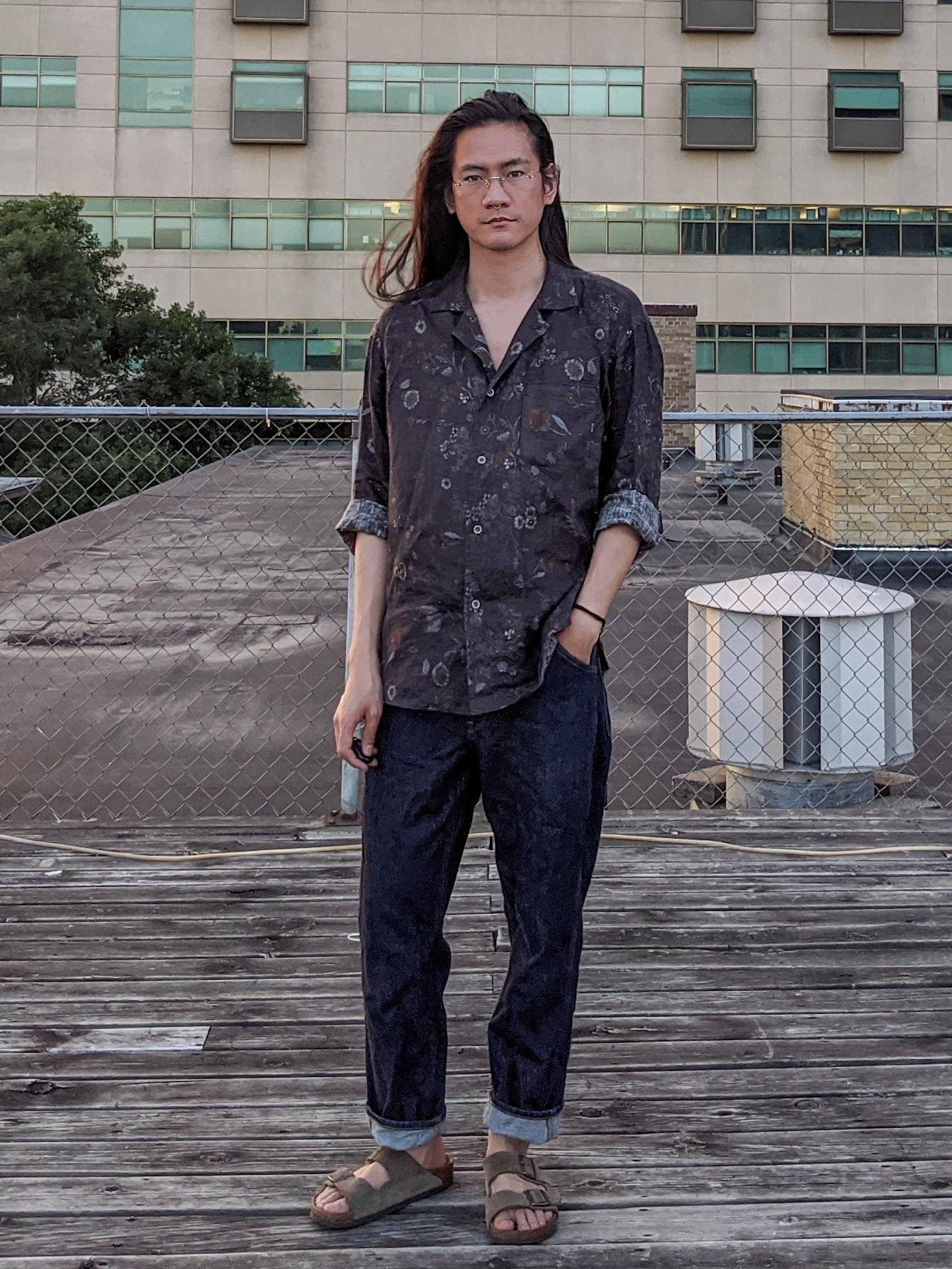 @_Donnyq wears a print shirt and dark jeans, and is photographed on a rooftop.