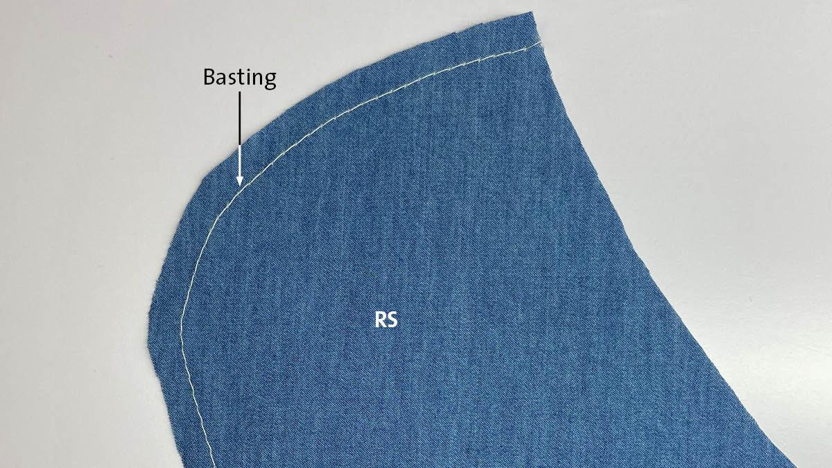 White machine basting along a blue garment piece's seamline