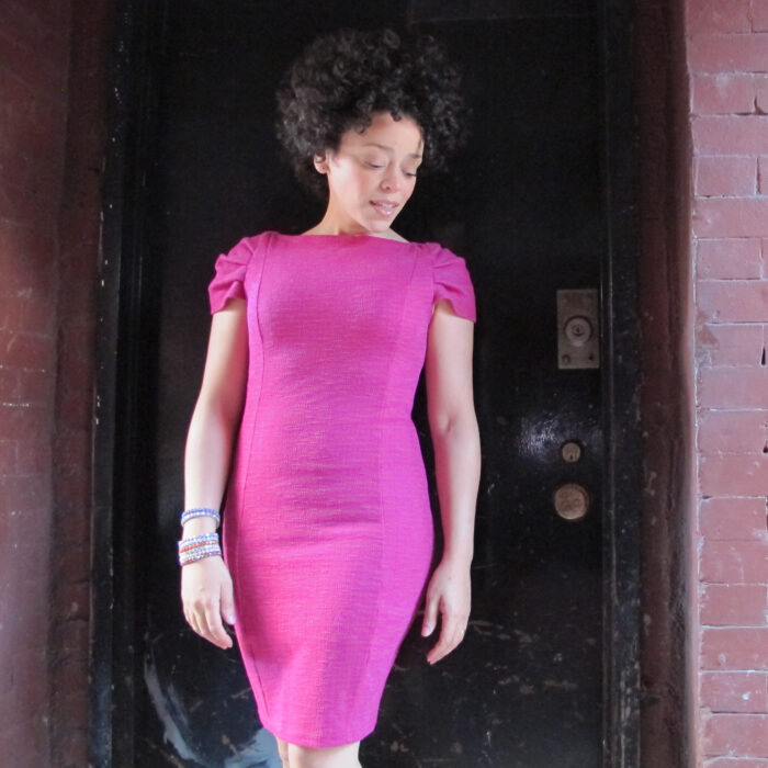 Marcy Harriell wearing a fuschia-colored princess-seamed sheath with gathered cap sleeves and little ease