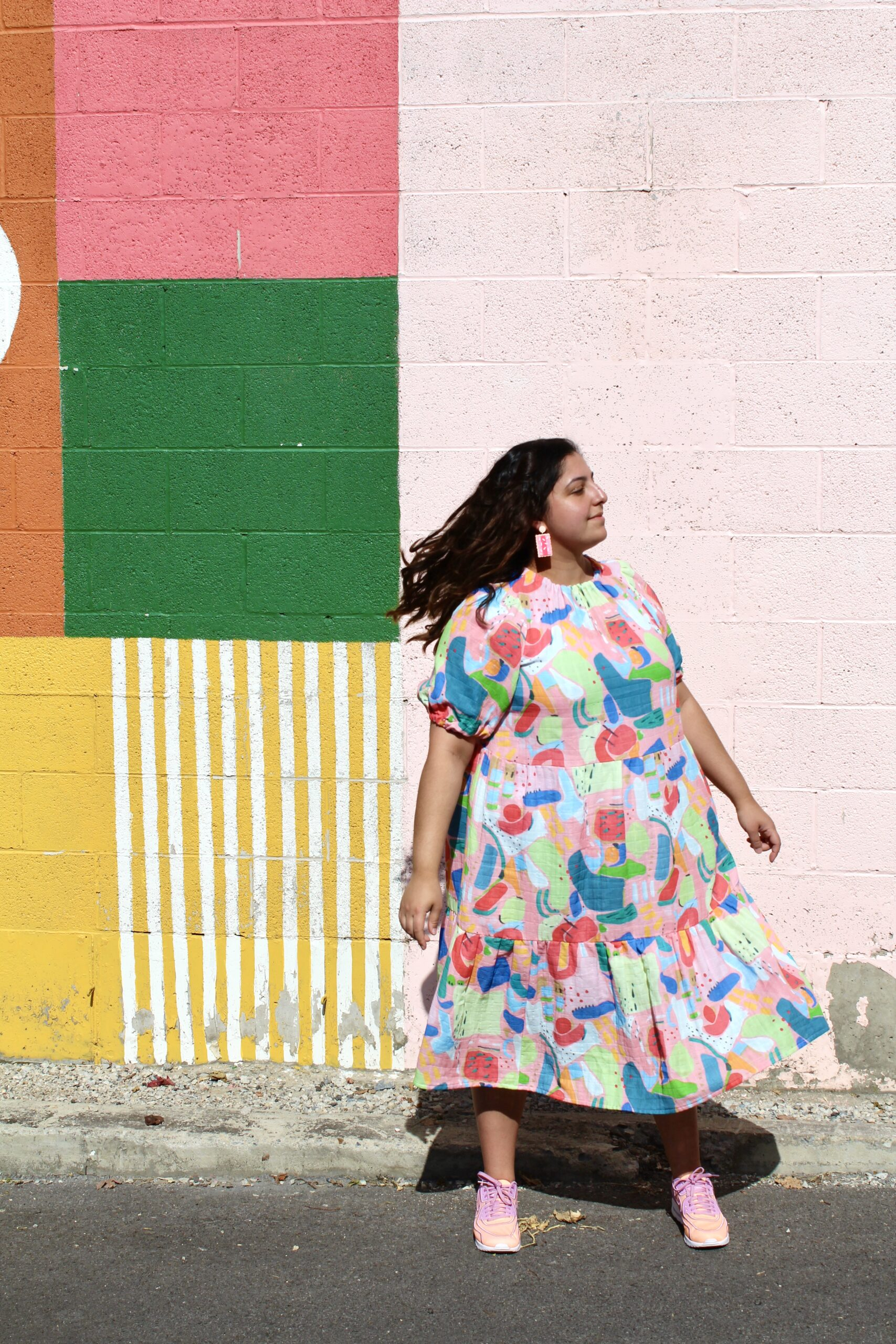 @sewlike, Romy-Krystal Cutler, in a bold printed dress, in front of a colorfully painted wall.