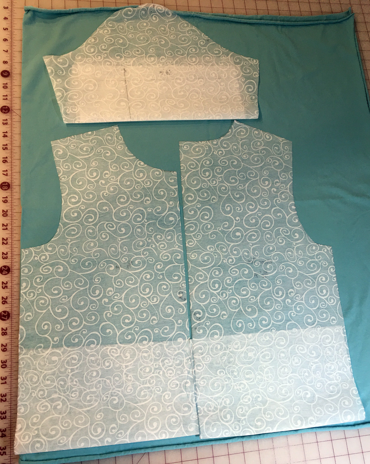 Top pattern pieces lying on blue jersey knit on gridded cutting mat