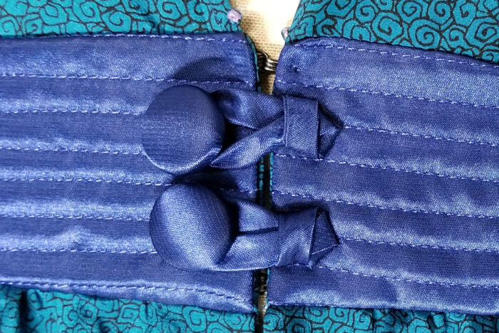 Gilbert Muniz version of a knotted button closure on a quilted waistband