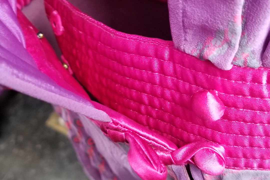 Close-up of hot pink quilted waistband at the button closures