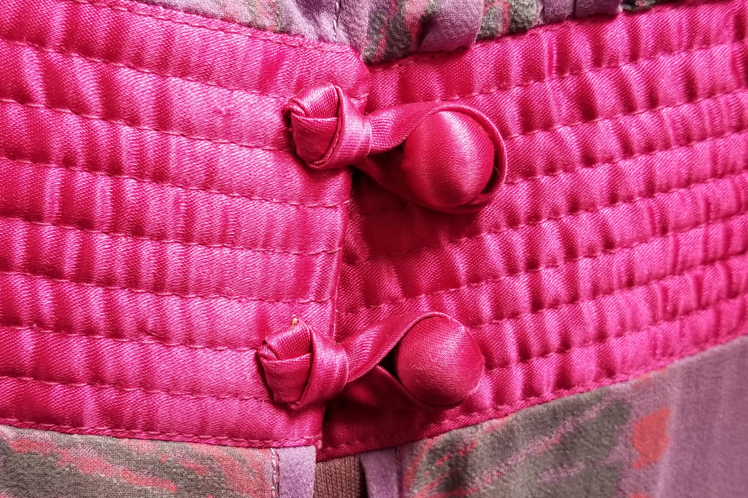Knotted loop button closure on the quilted waistband of a Zandra Rhodes dress