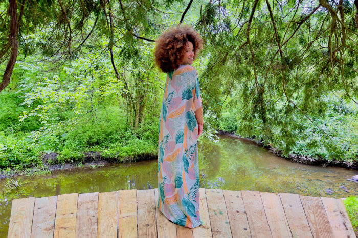 Marcy Harriell wearing a large-print caftan in a natural green scene