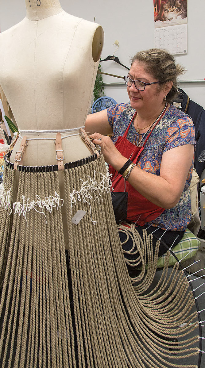 Woman working on a grasslands skirt for The Lion King.
