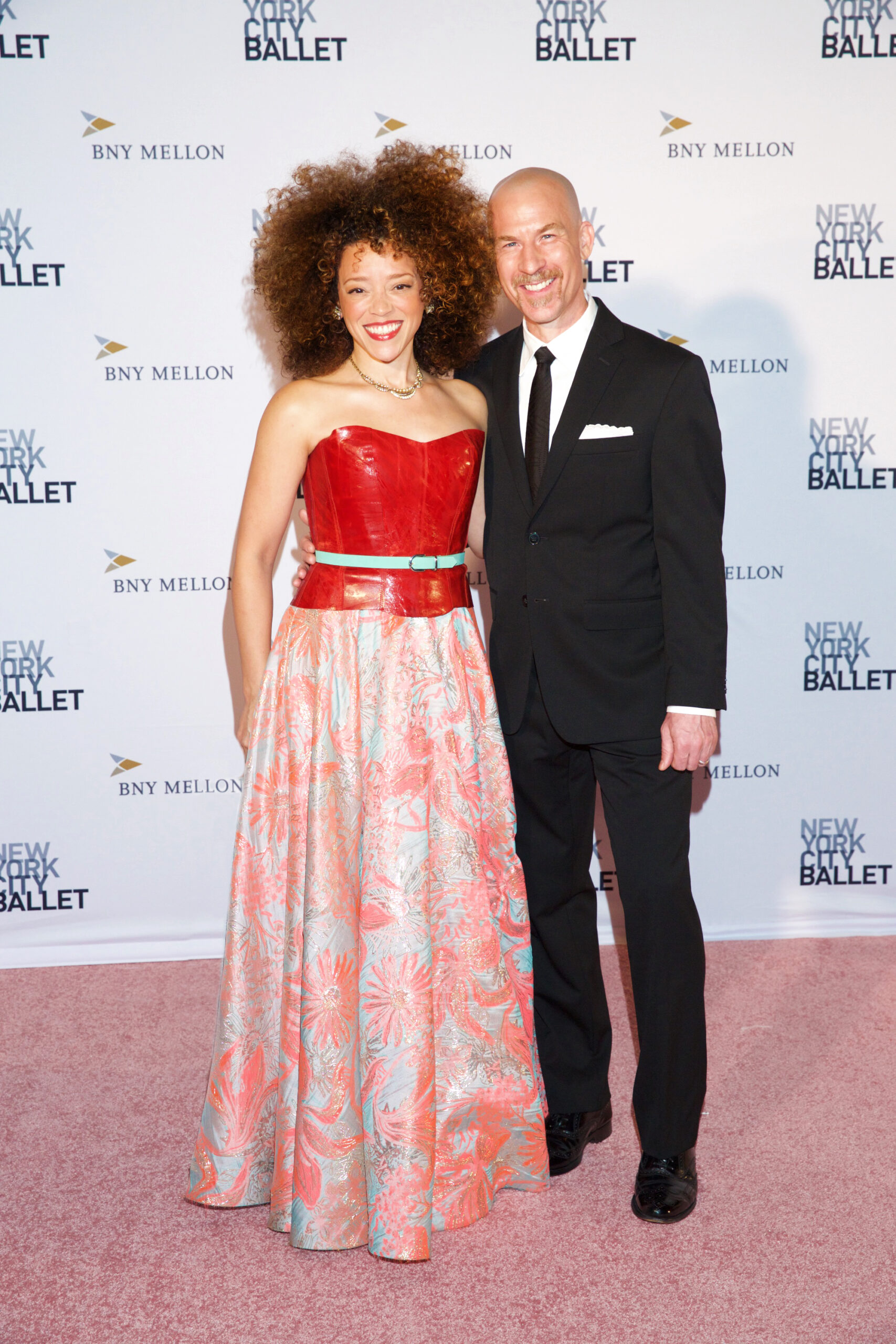 Marcy and Rob Harriell in formal outfits in front of New York City Ballet gala backdrop.