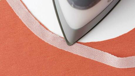 Tap the hot iron tip along the fusible stay tape to affix it along the neckline.