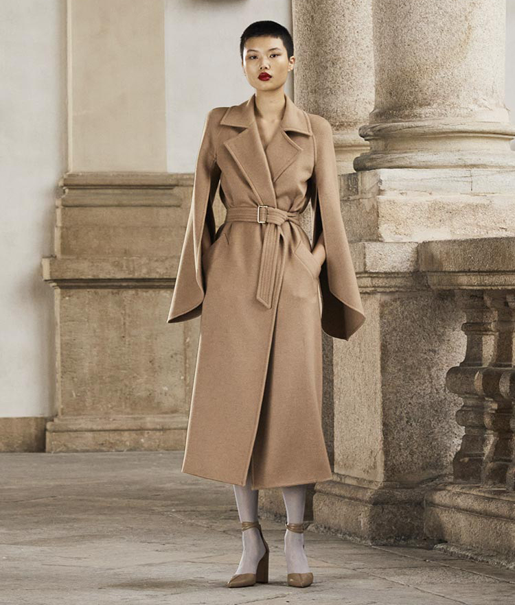 Model wears a long belted brown coat with long, two-piece sleeves.