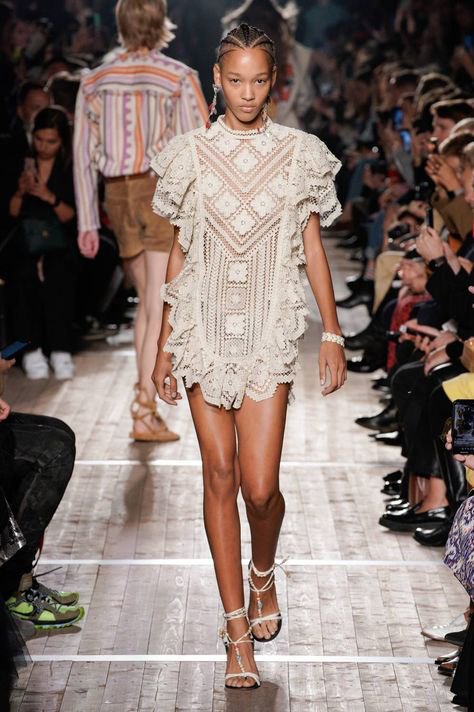 Model on runway wearing white lace tunic by Isabel Marant