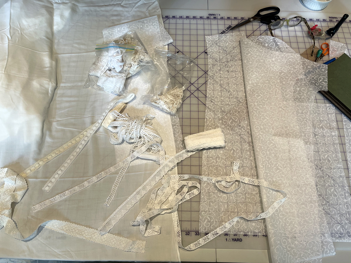 white fabric, laces, pattern pieces laying in a jumble on a gridded cutting mat