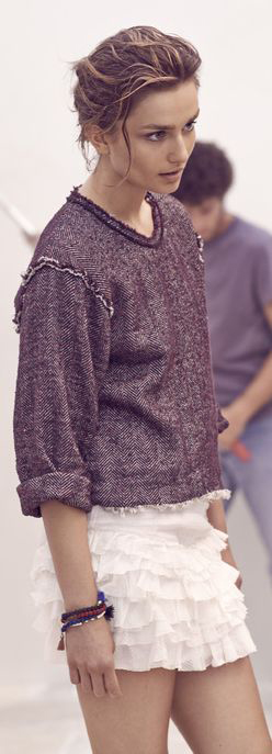 Model wears a gray sweatshirt and white ruffled miniskirt