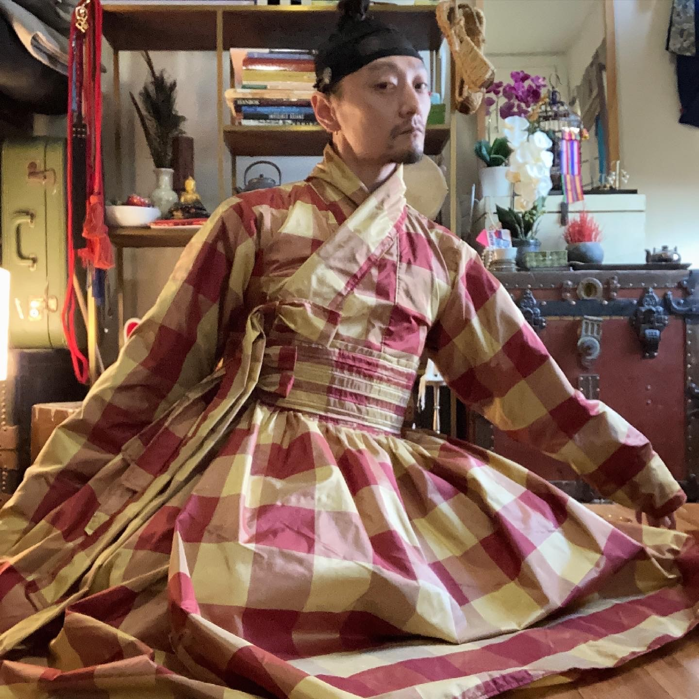 @yang_cheon_shik in plaid hanbok, seated on the floor of an interior space with Asian-inspired decor.