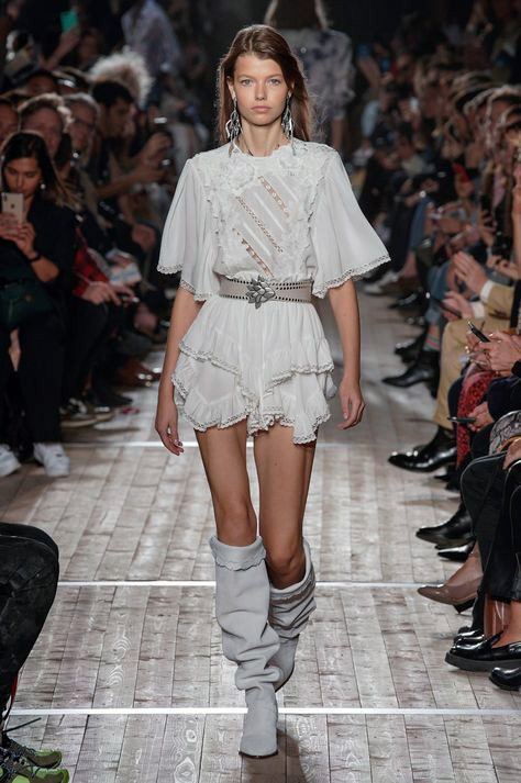 White lace and ruffled dress modeled on the runway inspired creation of a flowing tunic and tailored vest