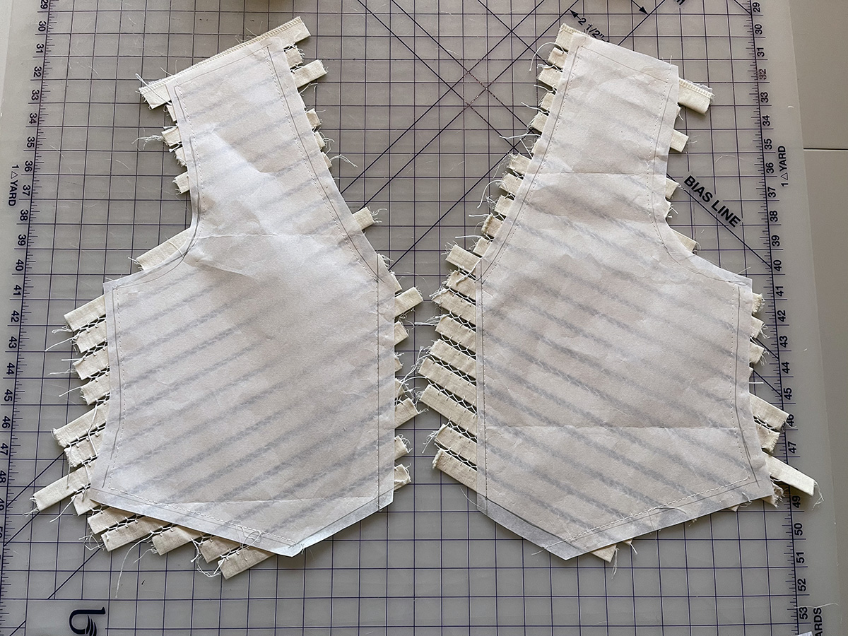 Delicate stitching connecting fabric strips on vest fronts are basted to interfacing