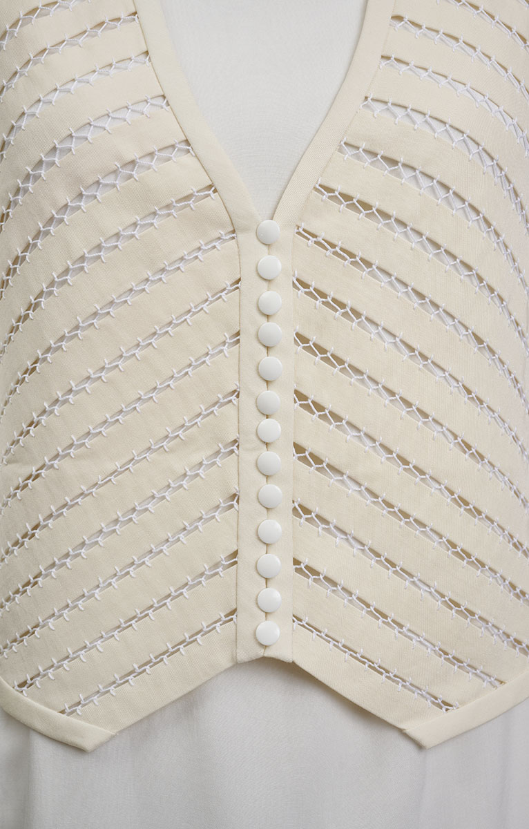 Close-up of delicate stitching called fagoting on vest front